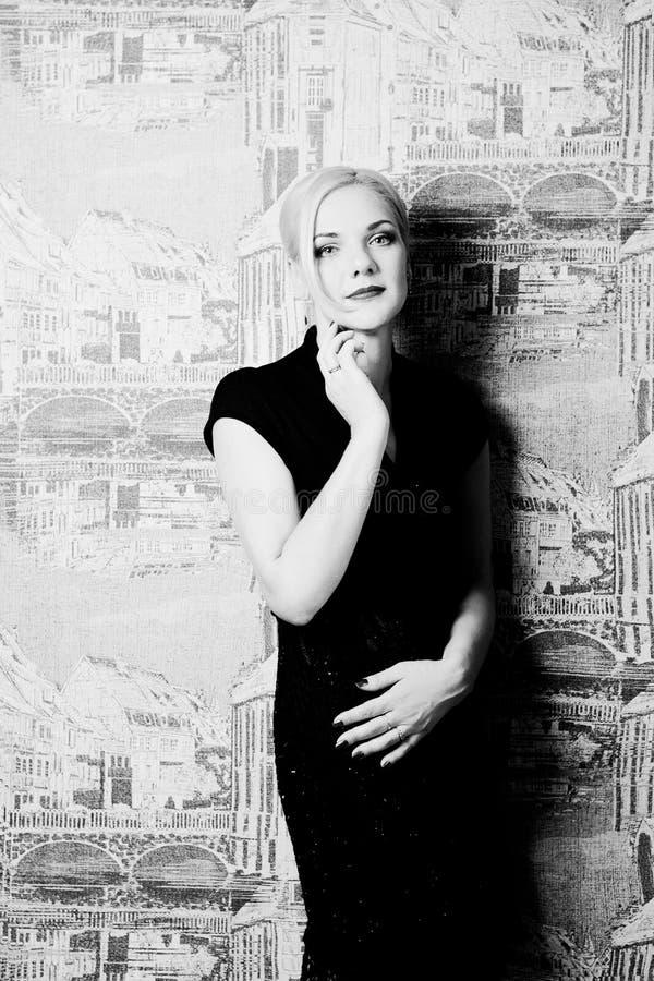 Blonde en vestido negro en blanco y negro interior fotos de archivo libres de regalías