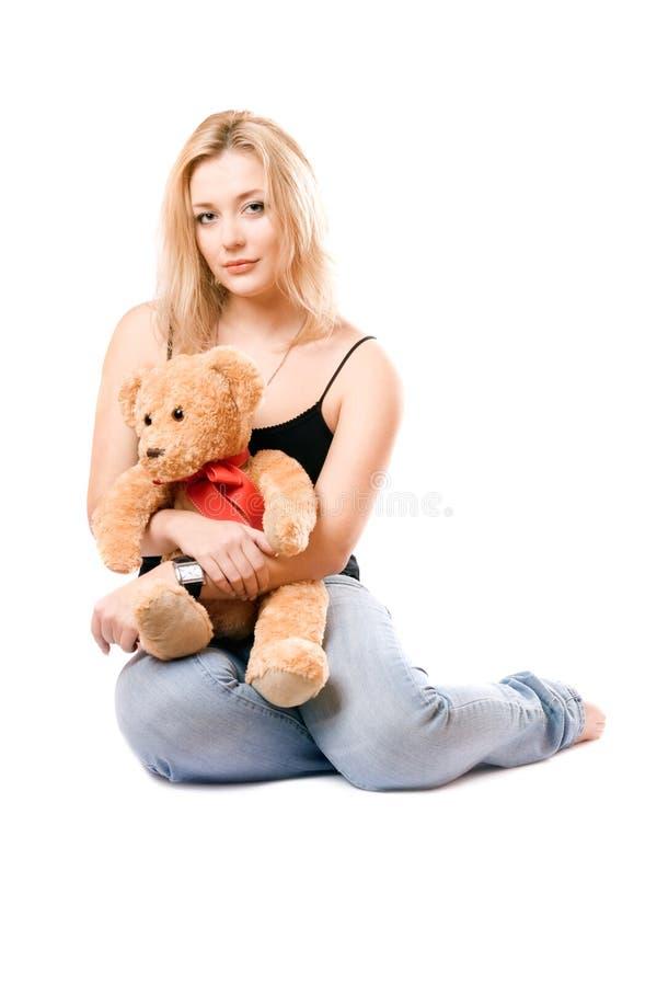 Blonde encantador con un oso de peluche foto de archivo