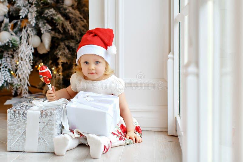Blonde encantador de la niña en un sombrero, la sonrisa y sentarse de Papá Noel foto de archivo