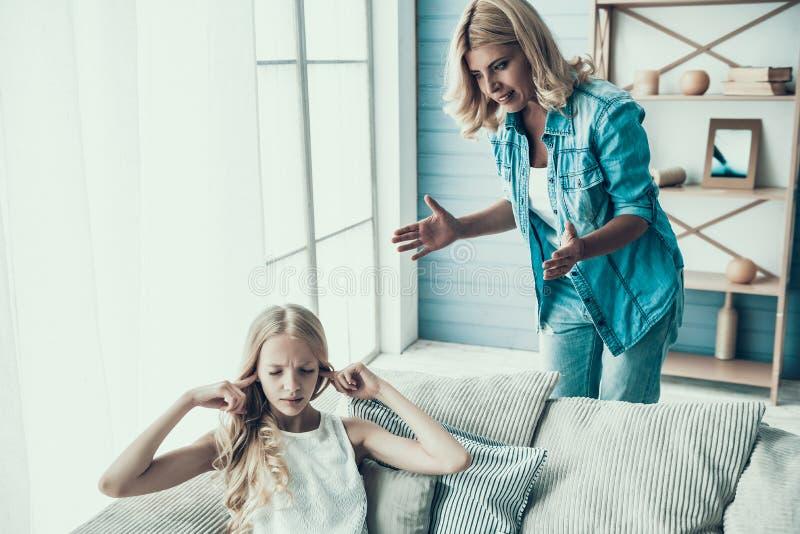 Blonde erwachsene Mutter holt oben frechen Mädchenjugendlichen stockbild