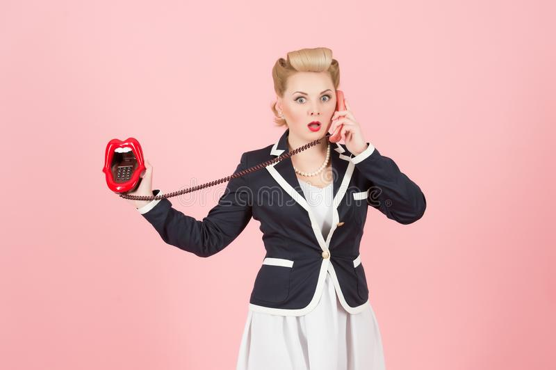 Blonde expressive girl in vintage style calling with cord lips phone. Pin-up make up with red lips and vintage telephone girl. stock photo
