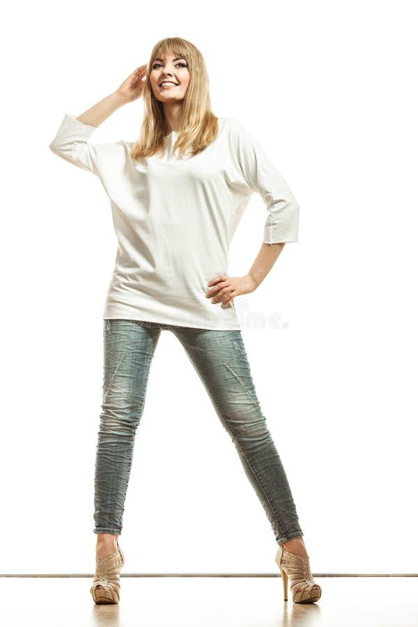 Blonde fashion woman in white shirt denim pants. Fashion. Young blonde woman denim pants white bat sleeve top high heels. Female model posing in full length stock images