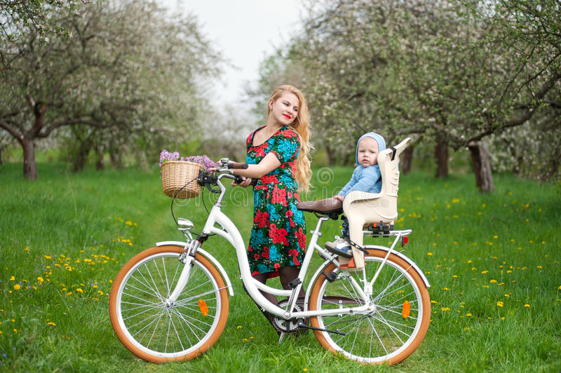 Blonde female with city bicycle with baby in bicycle chair. Happy mother in flowered dress holding bike and looking at child who sits in bicycle chair, against stock images