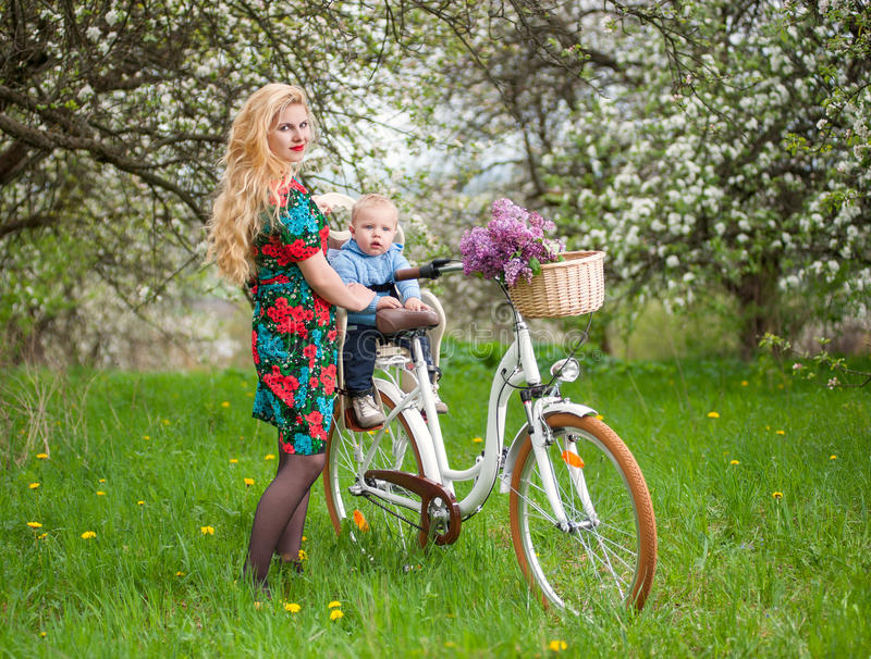 Blonde female with city bicycle with baby in bicycle chair. Young blonde mother with long hair and red lips in flowered dress holding son in bicycle chair, in stock images