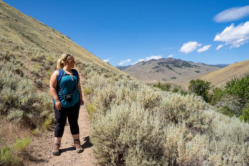 Blonde female hiker 30s looks off into the distance while on a mountain hike. Taken in the Salmon-Challis National Forest of. Idaho on Goldbug Hot Springs trail stock photography