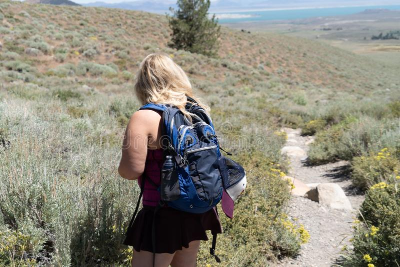 Blonde female hiker wearing backpack looks off in the distance, preparing for a long hike. Blonde female hiker wearing backpack looks off in the distance while stock photos