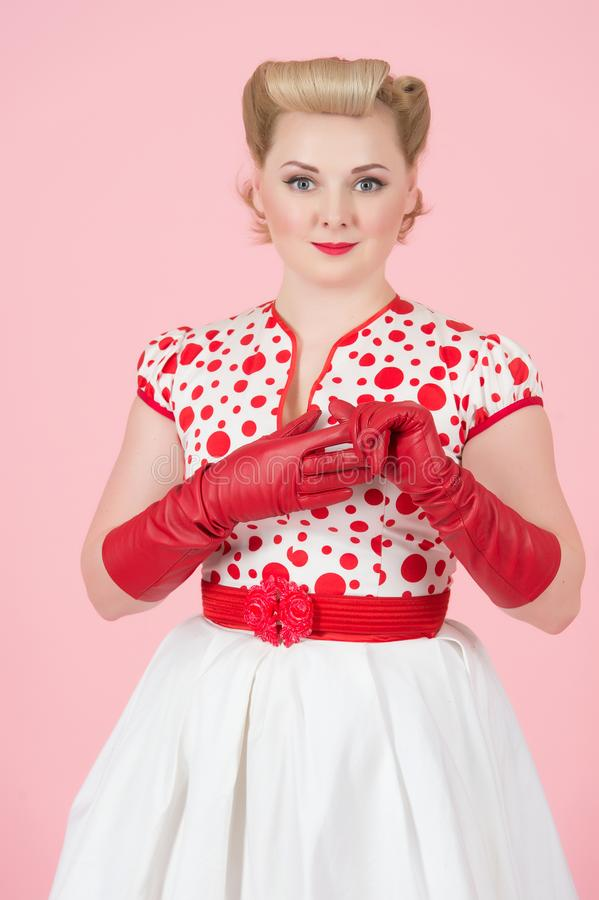Blonde female pin-up styled pretty woman removes the red glove from the hand isolated in studio with pastel pink background stock images