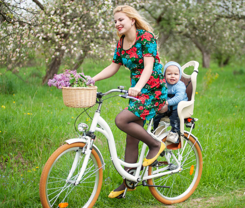 Blonde female riding city bicycle with baby in bicycle chair. Blonde female with long hair in dress riding city bicycle with baby in bicycle chair, in the basket stock photos