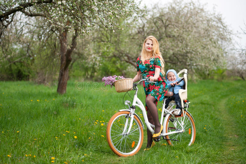 Blonde female riding city bicycle with baby in bicycle chair. Mother with long blonde hair in dress keeps bicycle and baby in bicycle chair, in the basket lay a stock photos
