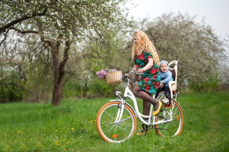 Blonde female riding city bicycle with baby in bicycle chair. Young mother with long blonde hair in dress riding city bicycle with baby in bicycle chair, against royalty free stock image