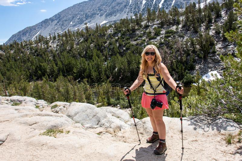 Blonde female stands on a boulder in the John Muir Wilderness in the Eastern Sierra Little Lakes Valley trail in California royalty free stock image