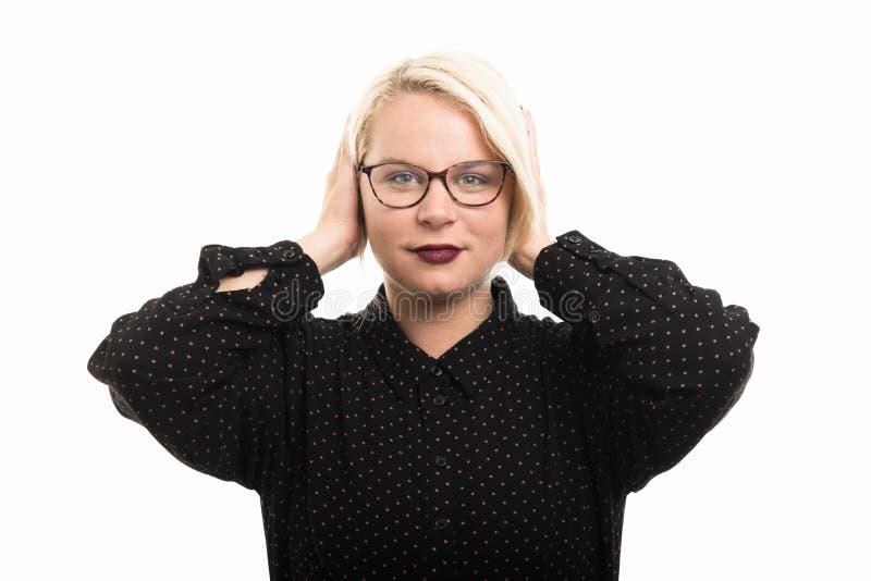 Blonde female teacher wearing glasses covering ears like deaf ge royalty free stock image