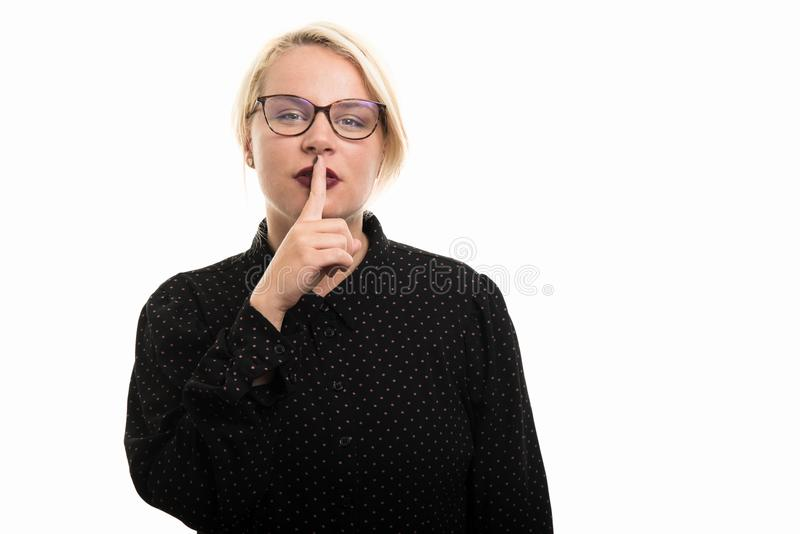 Blonde female teacher wearing glasses showing silence gesture royalty free stock images