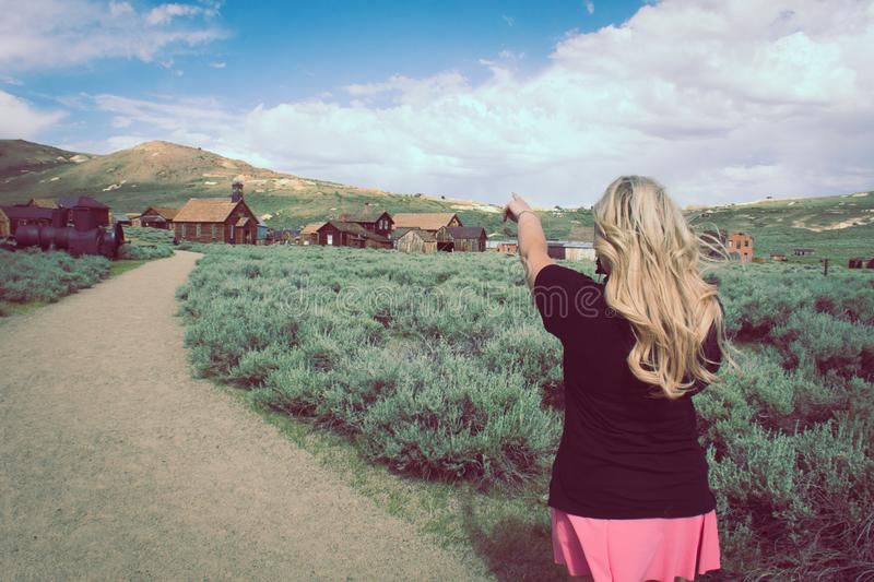 A blonde female tourist points to more abandoned buildings in the ghost town of Bodie California.  royalty free stock images