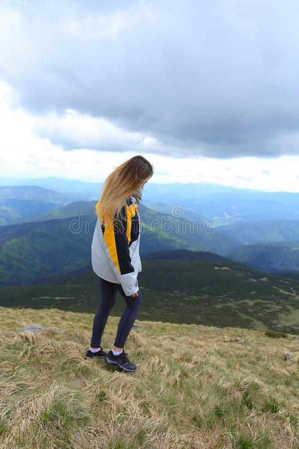 Blonde female tourist wearing yellow jacket standing in Alps mountains. Blonde female tourist wearing yellow jacket standing in mountains. Concept of spending royalty free stock image
