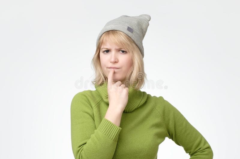 Blonde female wearing green sweater with puzzled expression, keeps finger on lips royalty free stock photos