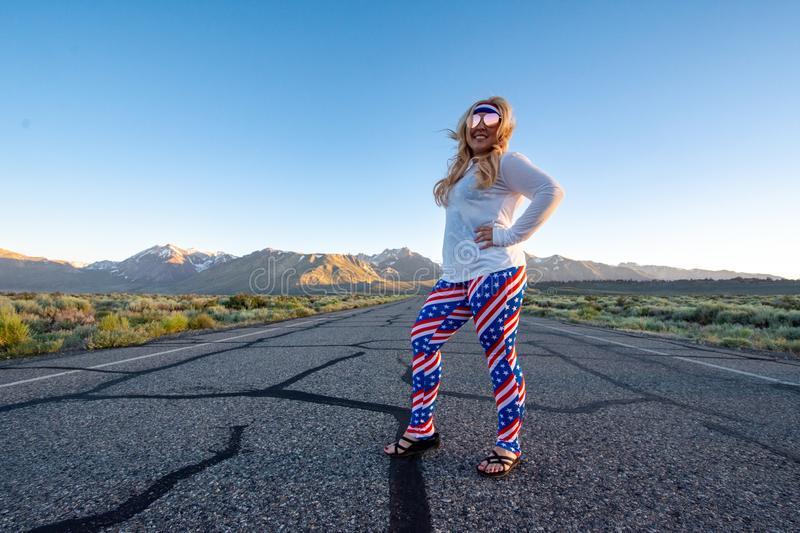 Blonde female wearing patriotic American clothing costume stands in the middle of a mountain road, concept for freedom and travel royalty free stock photo