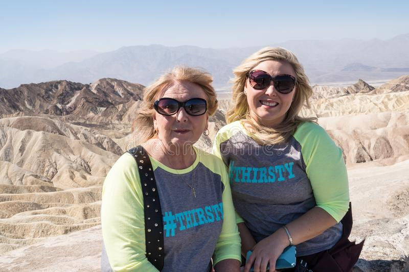 Blonde females mother and daughter pose for a photo at scenic overlook - Zabriskie Point in Death Valley National Park stock photography