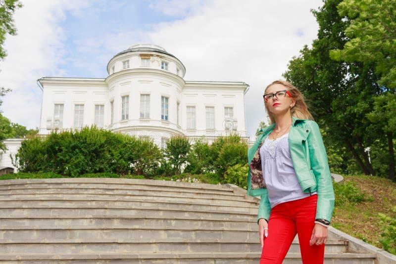 Blonde fino encantador joven de la mujer en la chaqueta de cuero y los vaqueros rojos que presentan cerca del palacio fotos de archivo