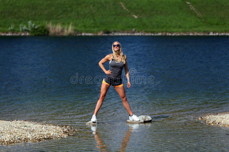 Blonde fitness girl standing at a river royalty free stock images