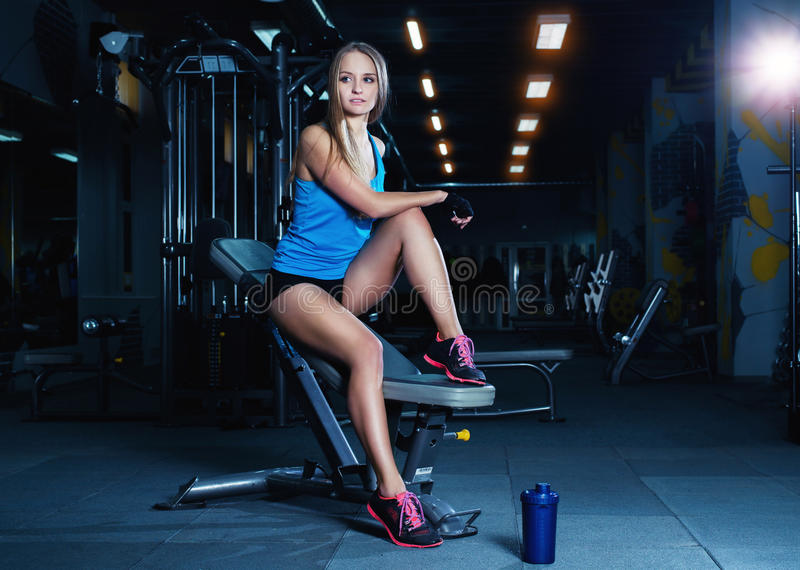 Blonde fitness woman in sportswear with perfect body posing in the gym. Attractive sporty girl resting after sport workout stock image