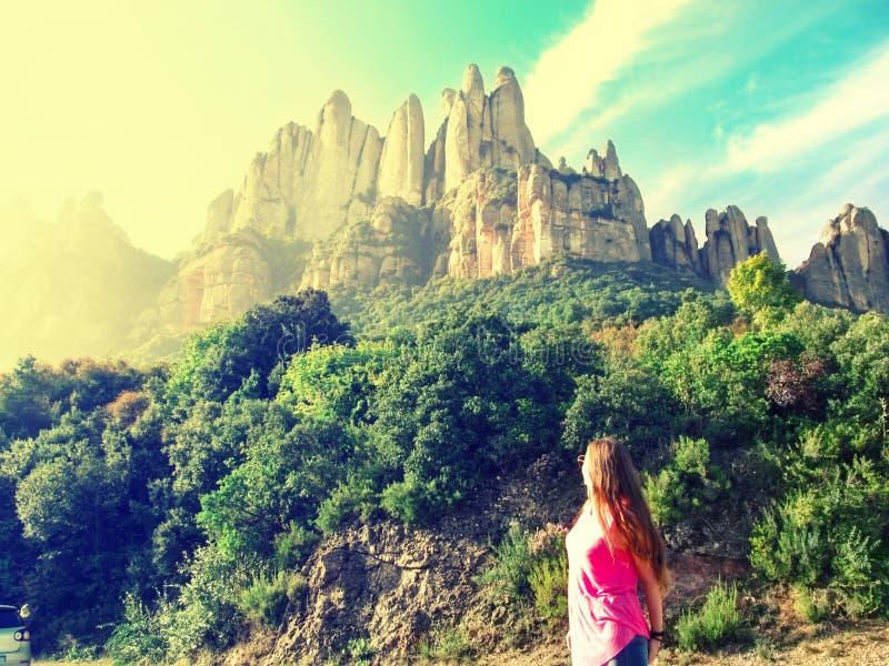 Blonde-flickan tittar på Mountain Montserrat i Katalonien i Spanien och solen skiner i ansiktet, på sidan. vackert berg arkivbild