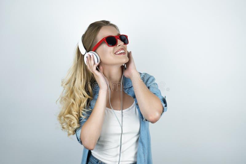 Blonde Frau in den Kopfhörern und in der Sonnenbrille hörend auf lächelnden weißen lokalisierten Hintergrund der Musik stockbilder