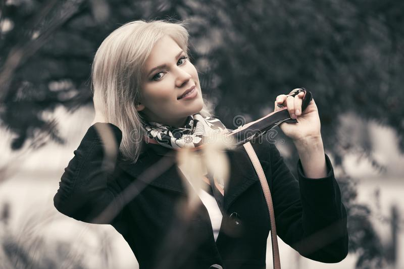 Blonde Frau der glücklichen jungen Mode, die in Herbstpark geht lizenzfreies stockbild