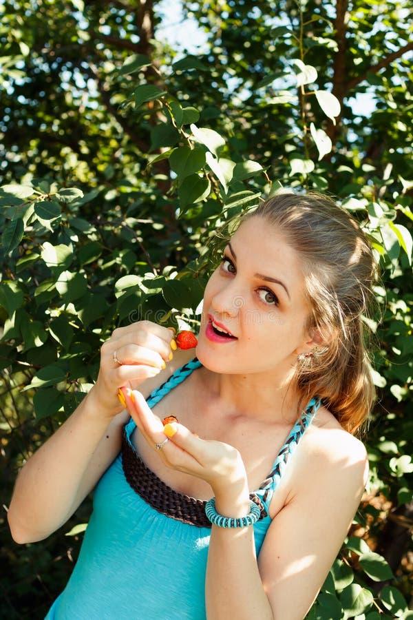 Blonde Frau der Junge recht, die Erdbeere isst lizenzfreie stockbilder