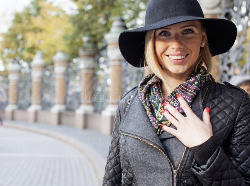 Blonde Frau der Junge recht im stilvollen Hut, europäisches kühles Wetter der Straßenmode, Stadtlebenfeiertag lizenzfreie stockfotos
