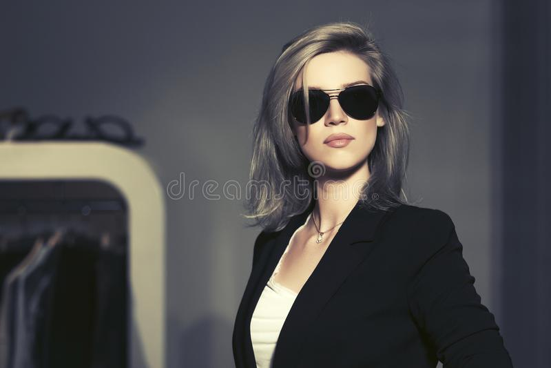 Blonde Frau der jungen Mode in der Sonnenbrille im Mallinnenraum stockbild