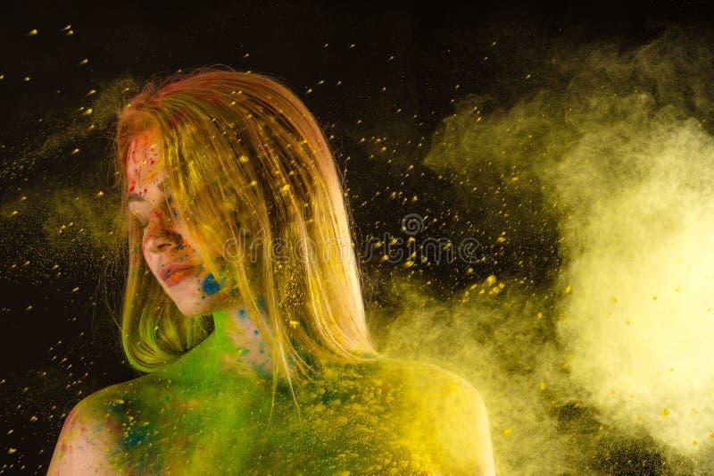 Blonde Frau der Mode in den Farben Holi stockfotos