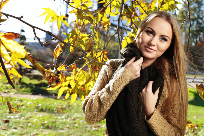 Blonde Frau in der zufälligen gemütlichen Kleidung, werfend im Herbstpark auf stockfoto
