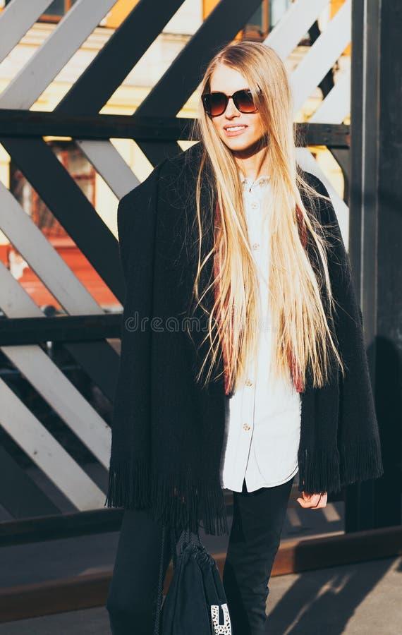Blonde Frau des jungen langen Haares in der Sonnenbrille und eine moderne Ausstattung, die am warmen Frühlingsabend der Straße au stockfoto