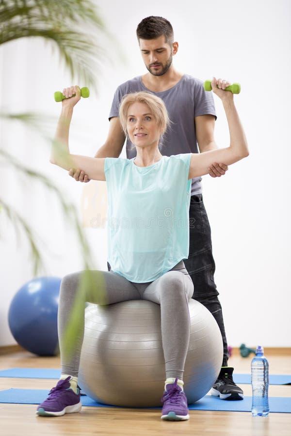 Blonde Frau des Mittelalters, die auf gymnastischem Ball w?hrend der Sitzung mit Physiotherapeuten trainiert lizenzfreie stockbilder