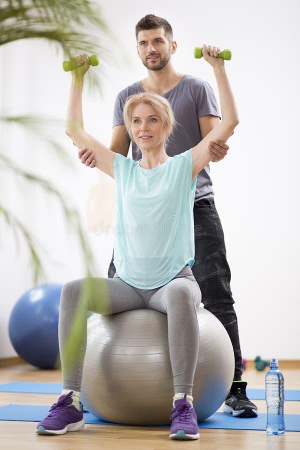 Blonde Frau des Mittelalters, die auf gymnastischem Ball w?hrend der Sitzung mit Physiotherapeuten trainiert stockfotografie