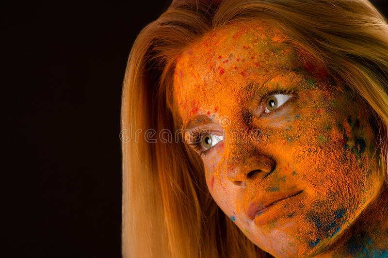 Blonde Frau des Porträtgesichtes in den roten Farben Holi lizenzfreies stockfoto