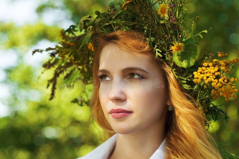 Blonde Frau des Porträts mit einem Kranz von Blumen auf Kopf lizenzfreies stockbild