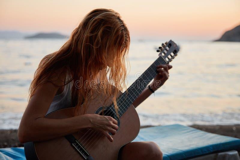 Blonde Frau, die Akustikgitarre auf dem Strand spielt lizenzfreie stockfotos
