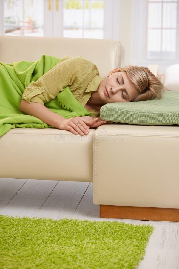Blonde Frau, die auf Couch schläft lizenzfreie stockbilder