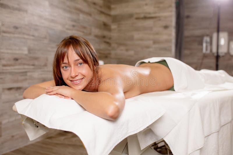 Blonde Frau, die auf der Massagetabelle liegt und die Kamera betrachtet stockfoto