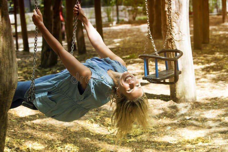 Blonde Frau, die auf einem Schwingen im Spielplatz sitzt lizenzfreie stockfotografie