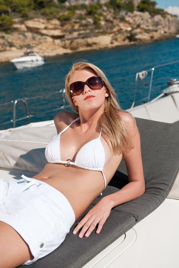 Blonde Frau, die auf Luxuxyacht mit Bikini ein Sonnenbad nimmt stockfoto