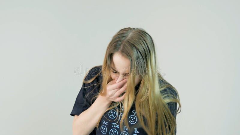 Blonde Frau, die auf weißem Hintergrund niest stockfotografie