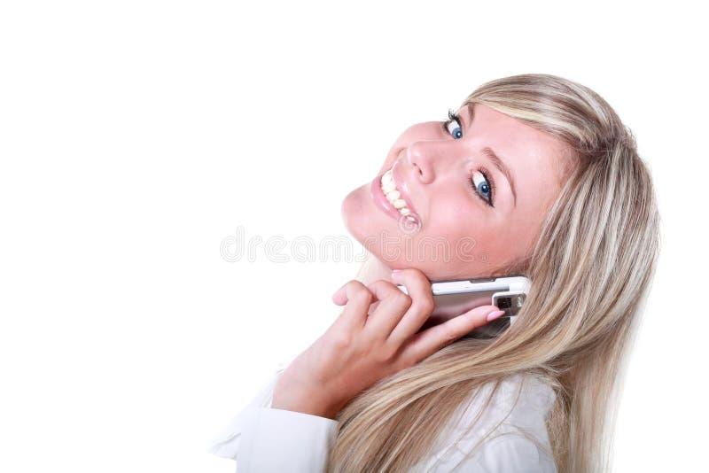 Blonde Frau, die durch Handy benennt stockfoto