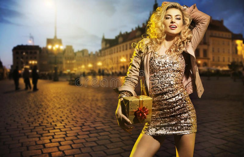 Blonde Frau, die ein kleines Geschenk hält lizenzfreie stockfotografie