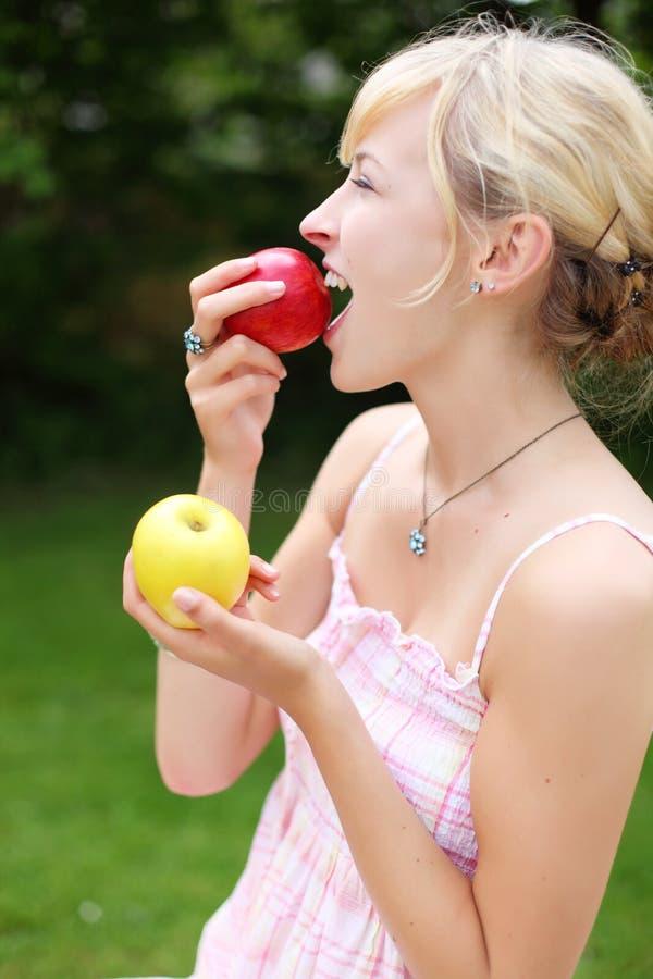 Blonde Frau, die einen frischen roten Apfel isst lizenzfreie stockfotos
