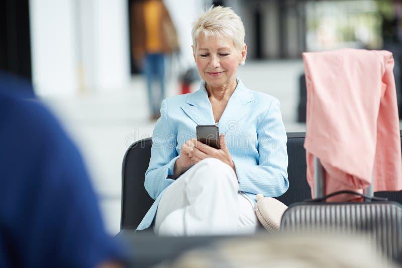 Blonde Frau, die Gerät im Flughafen verwendet stockfotografie