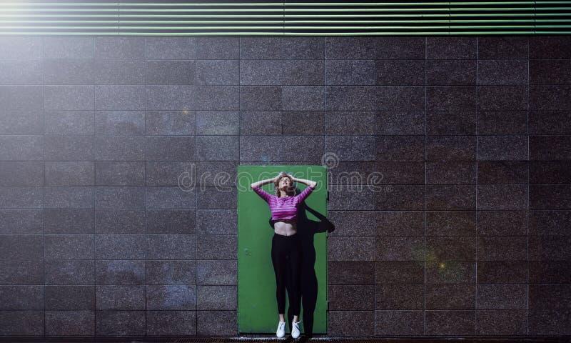 Blonde Frau, die herauf, gegen den stilvollen Grüntürhintergrund, im Freien springt lizenzfreie stockbilder