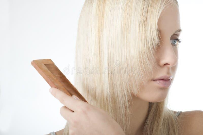 Blonde Frau, die ihr Haar aufträgt lizenzfreie stockfotografie
